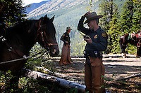 Reaching the Canadian border, officers from Whitefish MT Border Patrol, Spokane Sector dismount for a stretch.  They obtained four mustangs to ride rough back country to secure the northern border west of Glacier National Park to Canada.  They ride when they can to deter drug smuggling and illegals coming across the border.  The young horses were trained at a prison in Colorado and are sure footed.  Riding horses were James Perkins, Jeff Jude, Kevin Orr, Shawn Flannery.