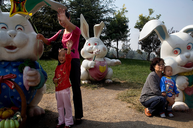 Visitors at the Tianjin Zoo pose for pictures with large sculptures of rabbits in Tianjin, China.