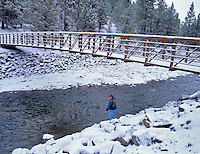Fly fisherman fishing in snow under bridge on Chewaucan River, Oregon.