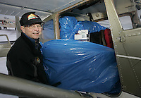 Saturday, Feb. 18, 2006  Anchorage, Alaska. Volunteer Iditarod Airforce pilot Bob Elliot loads straw into his Cessna plane prior to flying them  out to checkpoints along the trail.  Each musher is given one bale of straw at a checkpoint to bed their dogs down.