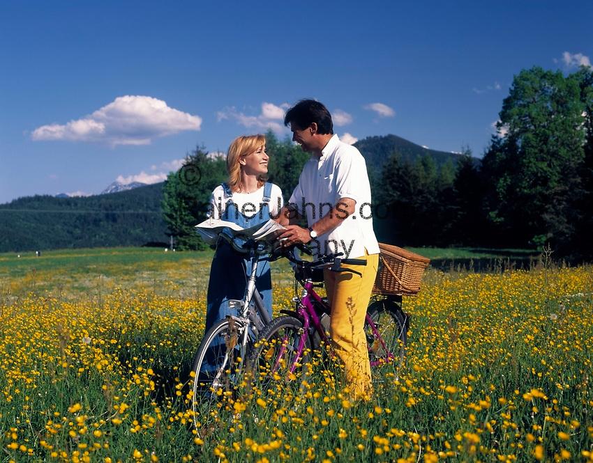 Paar mit Fahrraedern und Landkarte stehen in einer Blumenwiese   couple with bicycles and map standing in a flower meadow