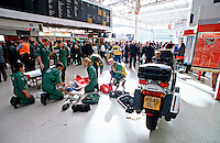 Paramedic ambulance crews attend a cardiac arrest victim on a train station platform. A paramedic is using the paddles of a defib to shock the victim. The rapid response paramedic motorcycle can be seen in the foreground. This image may only be used to portray the subject in a positive manner..©shoutpictures.com..john@shoutpictures.com