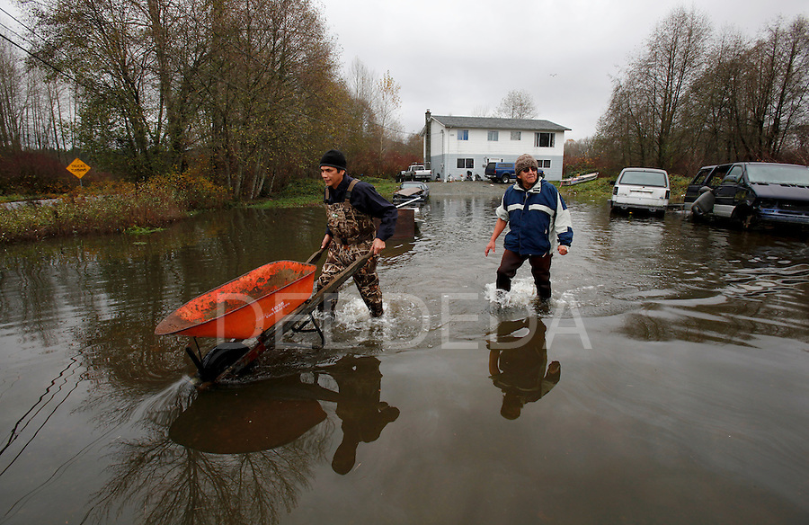 Wearing hip-waders, Eric Jones and Phillip Joe wade through the flood waters that has swamped their front yard, with a wheel barrow to collect sand bags on the Cowichan First Nation Reserve along Tzouhalem Road, the day after a state of emergency was called due to the flooding, in Duncan, BC British Columbia, Canada. Photo assignment for the Canadian Press (CP).