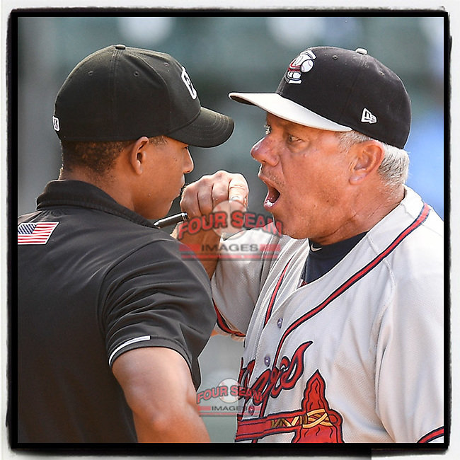 Rocket Wheeler (18), manager of the Rome Braves, has a word with home plate umpire Harley Acosta after a close call on a rundown in Game 1 of a doubleheader against the Greenville Drive on Friday, August 3, 2018, at Fluor Field at the West End in Greenville, South Carolina. Rome won, 7-6. (Tom Priddy/Four Seam Images)