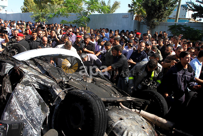 Palestinians stand around a car that exploded in Gaza City November 3, 2010. The car exploded outside a police headquarters in the city of Gaza on Wednesday, killing one Palestinian, Hamas officials and witnesses said. The Hamas Interior Ministry said the explosion was caused by an Israeli air strike . Photo by Ashraf Amra