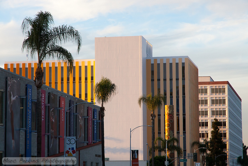 Looking north on Main Street in Santa Ana at sunset with a blue sky and wispy clouds in the background.  The golden building in the center is 1010 N. Main St, the Orange County School of the Arts.  Behind that is 1200 N. Main, including the Orange County Birth and Death registration office.  In the foreground is another Orange County School of the Arts building at 906 N. Main.
