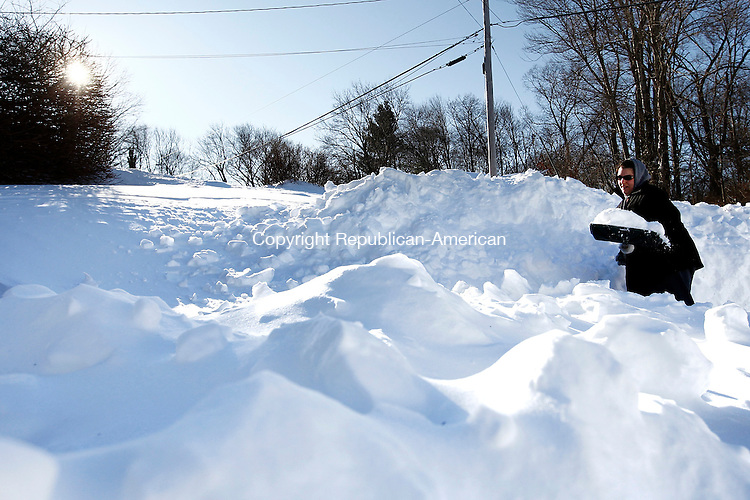 Naugatuck, CT- 09 February 2013-020913CM10-  A late afternoon sun begins to set as Michelle Keller of Naugatuck shovels the way out of her driveway Saturday afternoon in Naugatuck.  Residents were digging themselves out after a blizzard dumped more than two feet of snow in the area.   Christopher Massa Republican-American