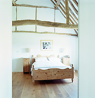 The double-height master bedroom has an original vaulted ceiling with exposed beams
