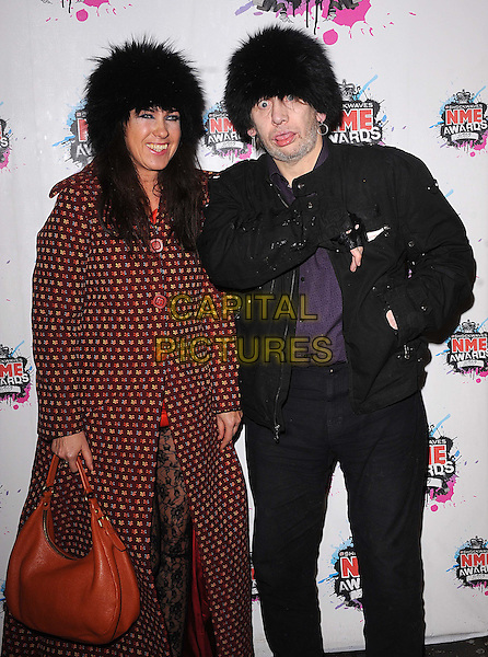 GUEST & SHANE MacGOWAN.The Shockwaves NME Awards 2010 held at Brixton Academy, London, England..February 24th, 2010.half length black jacket hat fur furry red maroon pattern orange bag purse jeans denim mouth open tongue funny .CAP/BEL.©Tom Belcher/Capital Pictures.