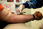 phlebotomist drawing blood from arm of male patient with tourniquet, hand holding tennis ball