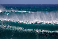 Surfers narrowly escaping a big set on the outer reef at Pipeline, North Shore, Oahu