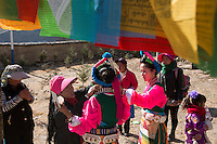 East Village, Diqing Tibetan Autonomous Prefecture, Yunnan Province, China - Tibetan woman, under a stupa, prepare to perform traditional Xianzi Dance, February 2017.