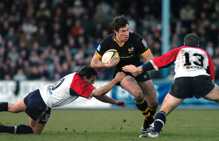 Photo. Glyn Thomas. .Bristol Shoguns v London Wasps. .Powergen Cup, Sixth Round. 19/12/2004..Wasps' Tom Voyce (C) is tackled by Jason Strange (L) and Rob Higgitt.