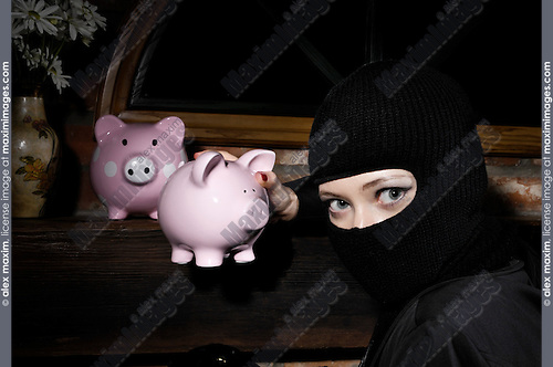 Caught by surprise burglar stealing piggy banks from a house at night