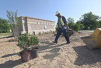 NWA Democrat-Gazette/FLIP PUTTHOFF <br />IN A ROUNDABOUT WAY<br />Heyi Gonzalez (cq) unloads plants Tuesday June 5 2018 during a landscaping project near downtown Rogers. Workers planted shrubs at the new roundabout at Arkansas Street and Monte Ne Road.