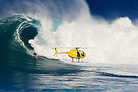A helicopter filming Laird Hamilton at Peahi (Jaws) off Maui. Hawaii.