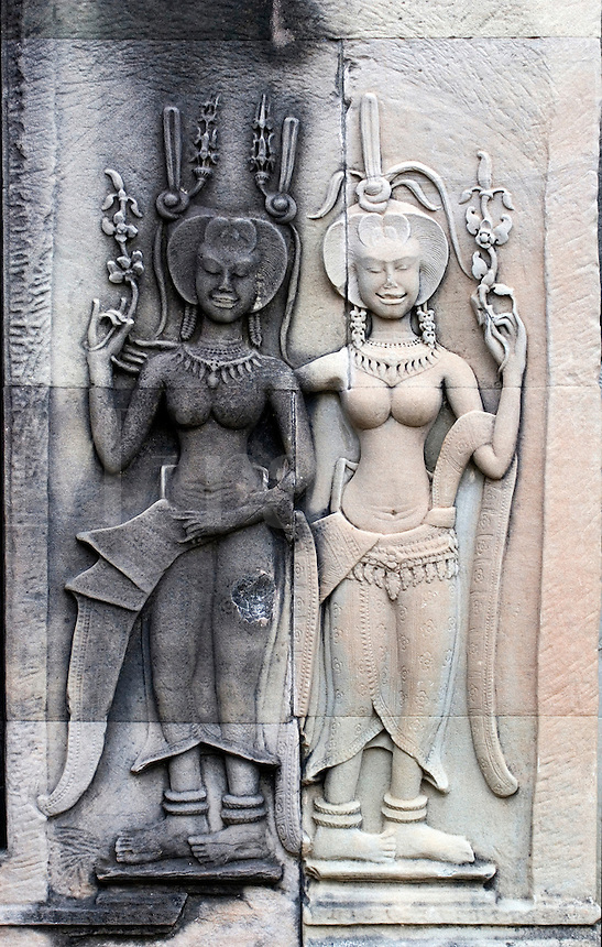Stone carved bas relief of two smiling Apsaras (celestial maidens) at Angkor Wat, built in the 11th century by Suryavarman the 2nd,  -  Cambodia.