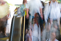 Commuters rush down the escalator at the station.