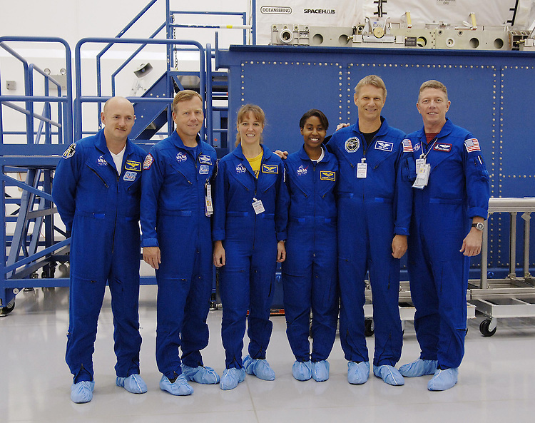 KENNEDY SPACE CENTER, FLA. At Astrotech Space Operations in Titusville, Fla., the STS-121 crew poses for a photo. From left are Pilot Mark Kelly, Mission Commander Steven Lindsey, and Mission Specialists Lisa Nowak, Stephanie Wilson, Piers Sellers and Michael Fossum. The STS-121 crew is at KSC to take part in Crew Equipment Interface Test activities, which provide hands-on experience with equipment they will use on-orbit. STS-121, the second Return to Flight mission, is targeted for launch in a lighted planning window of Sept. 9 to Sept. 25. CREDIT: NASA Kennedy Space Center (NASA-KSC)