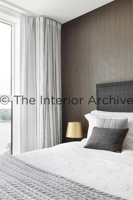 A bedroom with a grey patterned wallcovering and a double bed with an upholstered headboard in a check pattern fabric.