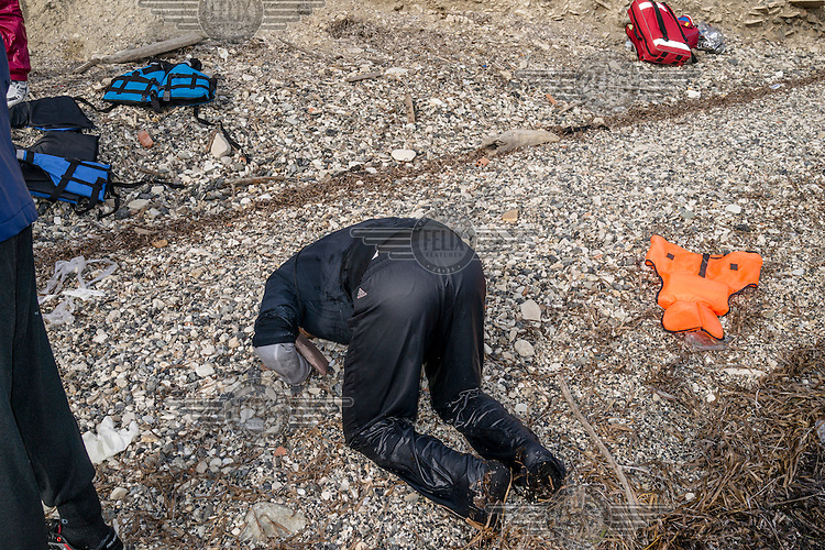 A man prays having just survived the Aegean Sea crossing on a boat from Turkey.