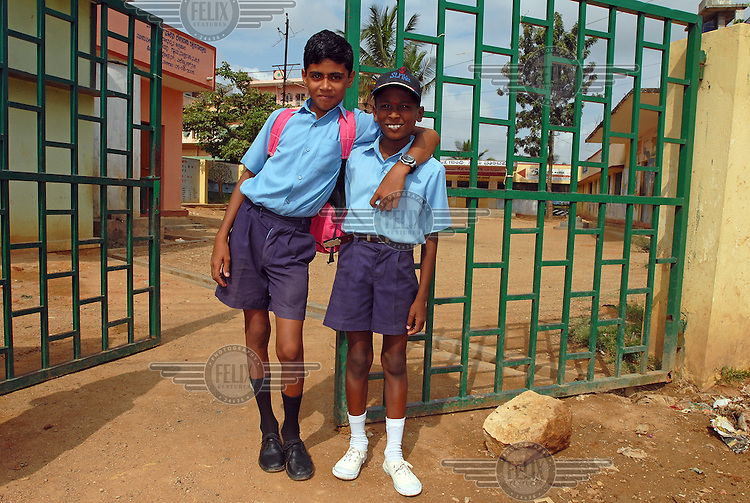 Two uniformed schoolboys stand at the gates of their school on the outskirts of 'Electronics City', an industrial complex dedicated to the IT and electronics industries. The 'Electronics City' complex, located ten miles outside Bangalore, has been hugely successful in attracting foreign investment and it is home to several multinational companies.