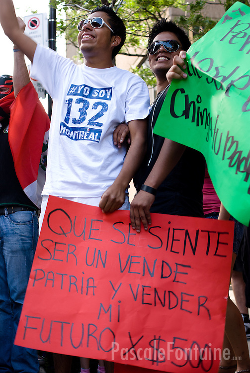 """Two young mexican men protest the election of Enrique Pena Nieto. Spanish sign says """"How does it feel to sell the country and my future for 500 $?""""."""