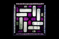 Detail of stained glass panel in purple and white geometric design in the church of Notre-Dame du Raincy on May 24, 2009 in Le Raincy, Seine Saint Denis, France. Built in 1922-1923 by the architects and brothers Auguste and Gustave Perret, the cathedral was the first one to be built with reinforced concrete. The stained glass was created by Marguerite Hure based on sketches by Maurice Denis. Picture by Manuel Cohen