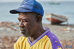 A year after Hurricane Matthew ravaged parts of Haiti, a fisher--razor blade in his mouth--mends his net on a beach in northwestern Haiti near the village of Plateforme. The village was ravaged in the storm, and Lutheran World Relief, a member of the ACT Alliance, has helped the community rebuild its economy with fishing materials, a solar-powered refrigerator room for storing their catch, and other assistance.
