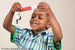 3 year old boy using bar magnet to pick up metal whistle horizontal
