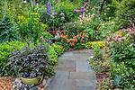Vashon-Maury Island, WA: Flagstone pathway through a summer perennial garden featuring dahlias. peonies; alstromeria; sedum; delphimium and allium
