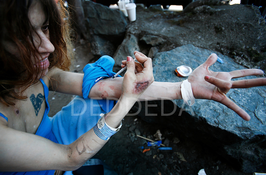 A prostitute injects a potent mixture of intravenous drugs into her arm at a littered shooting gallery in downtown Victoria, British Columbia, BC, Canada. Photo shot for the NATIONAL POST.