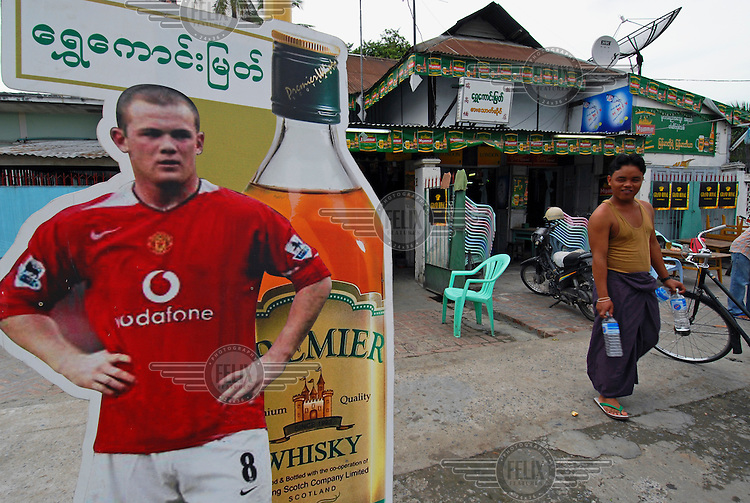 "A full size cutout of footballer Wayne Rooney promoting 'Premier' whisky, a local Myanmar brew that is allegedly made with Scottish ""co-operation""."