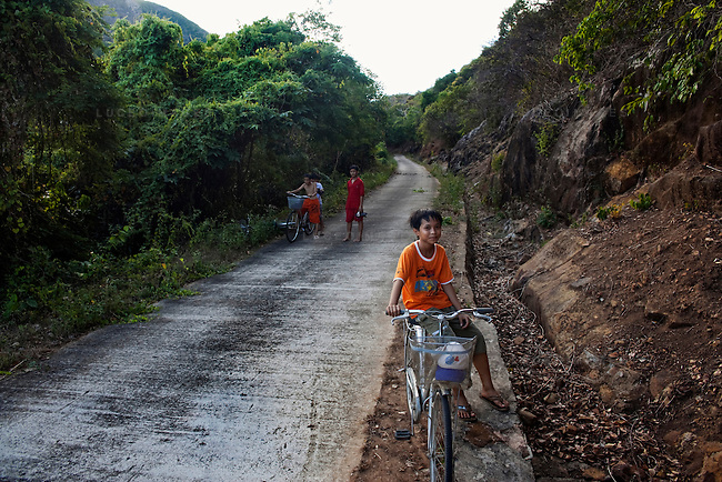 Local children ride their bicycles through the National Forest on Con Son Island, part of the Con Dao Islands.The 16 mountainous islands and islets are situated about 143 miles southeast of Ho Chi Minh City in Vietnam, in the South China. Photo taken Thursday, May 5, 2010...Kevin German / LUCEO For the New York Times