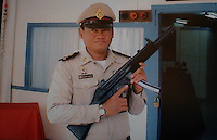 Thailand's only executioner Chawalate Jarubun of Bangkwang Central Prison poses at the door of the execution chamber  and with the machine gun that he has used to execute 55 prisoners. (best quality available)