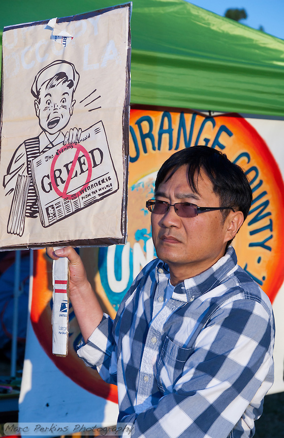 """A man walks in front of the bright orange """"Occupy Orange County - in unity with Occupy Wall Street"""" banner while holding a sign with a newspaper boy holding a paper with a graphical """"No greed"""" written on it."""