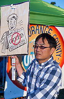 "A man walks in front of the bright orange ""Occupy Orange County - in unity with Occupy Wall Street"" banner while holding a sign with a newspaper boy holding a paper with a graphical ""No greed"" written on it."