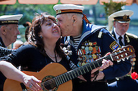 Moscow, Russia, 09/05/2011..A former sailor kisses a woman playing the guitar as Russian World War Two veterans and well-wishers gather in Gorky Park during the country's annual Victory Day celebrations.