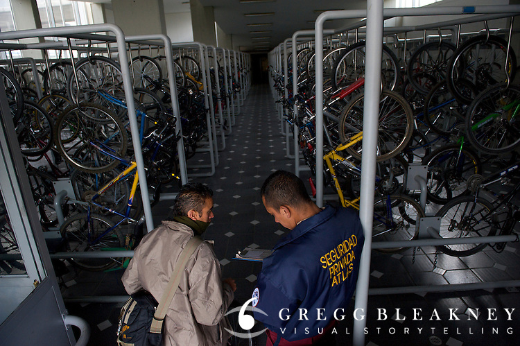 A man checks his bicycle into the transmilenio Bicycle to bus transfer station, Portal de Las Américas station's 700-bicycle storage facility  - Bogota - Colombia