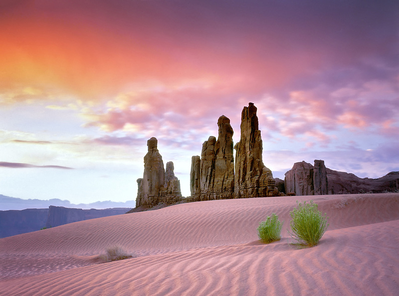 Sand dune and Totem Pole rock formation at sunrise. Monument Valley, Arizona