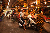 VIETNAM, Hanoi, young women stop their moped to buy meat from a butcher at the Chau Long Market