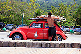 BRAZIL, Rio de Janiero, a man straps his board to the top of his car at Prainha Beach