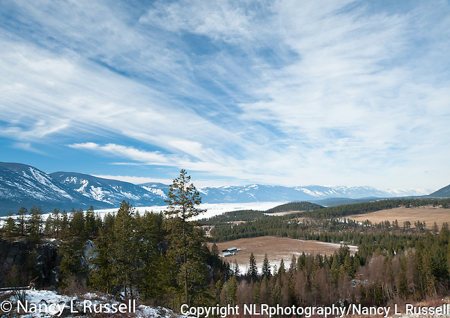 Winter scene of the Kootenai Valley in north Idaho with agricultural fields in the valley and snow covered Selkirk mountains