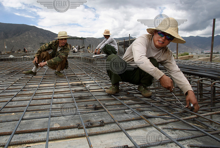 Chinese migrant workers help to erect a bridge that will link the new Lhasa railway station with the city centre.