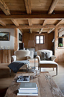 The first floor of the chalet consists of an open plan living/dining and kitchen area, furnished with contemporary armchairs and textured wooden pieces