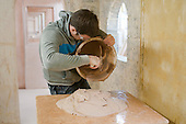 Plastering student pours out some fresh plaster, Able Skills, Dartford, Kent.