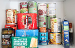 Tinned food piled up in domestic household kitchen cupboard including products from Tesco supermarket, UK