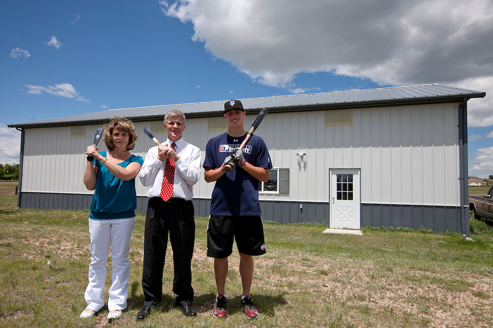 Brandon Nimmo, right, poses for a portrait with his parents, Patti and Ron Nimmo, outside the family's 2688 sq. ft. barn on Tuesday, June 21, 2011, in Cheyenne, Wyo. The barn houses a batting cage where Nimmo was able to perfect his left-handed swing growing up. The New York Mets selected Nimmo, who graduated from high school in May, at No. 13 overall in this year's MLB draft. (Photo by James Brosher)