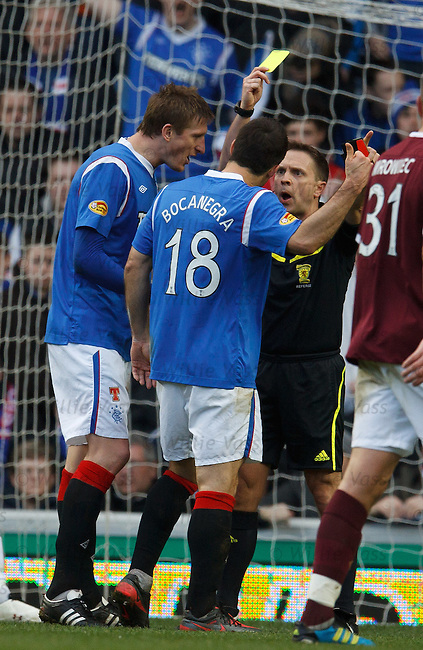Referee Crawford Allan yellow cards Carlos Bocanegra as Dorin Goian continues his protest over the penalty