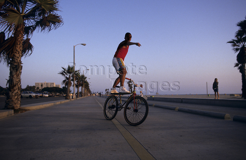 Young man performing tricks on his bike by the beach